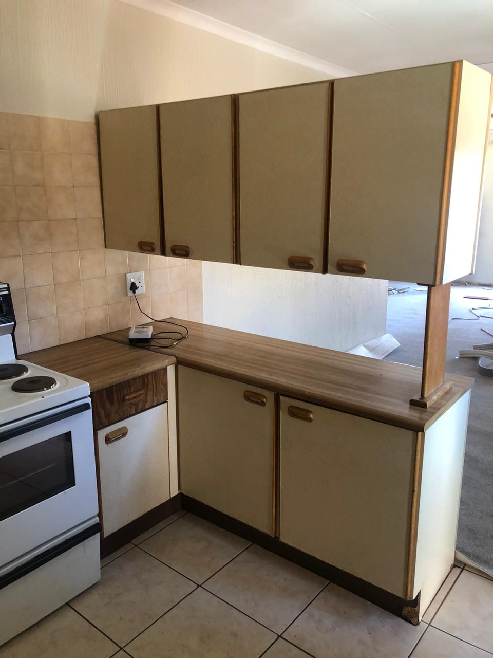 Kitchen cupboards , wooden flooring , sink, and stove