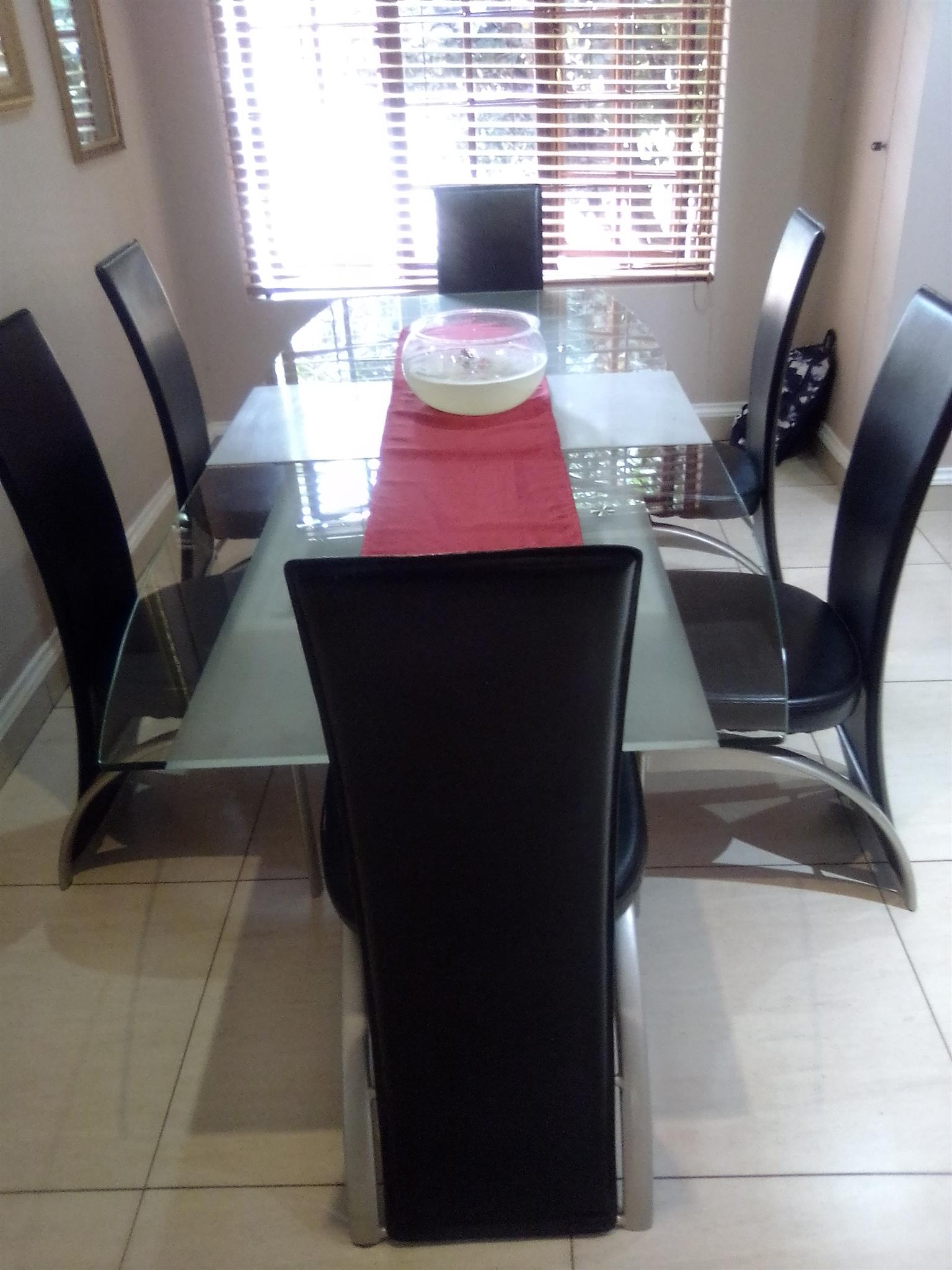 Beautiful 6 seater dining room suite, glass, black and silver for sale. Table extends