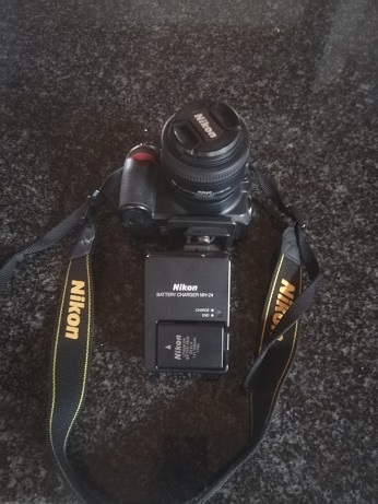 Nikon D3100 with a 18-55 VR lens, it includes the strap aswell as a battery  with it's charger | Junk Mail