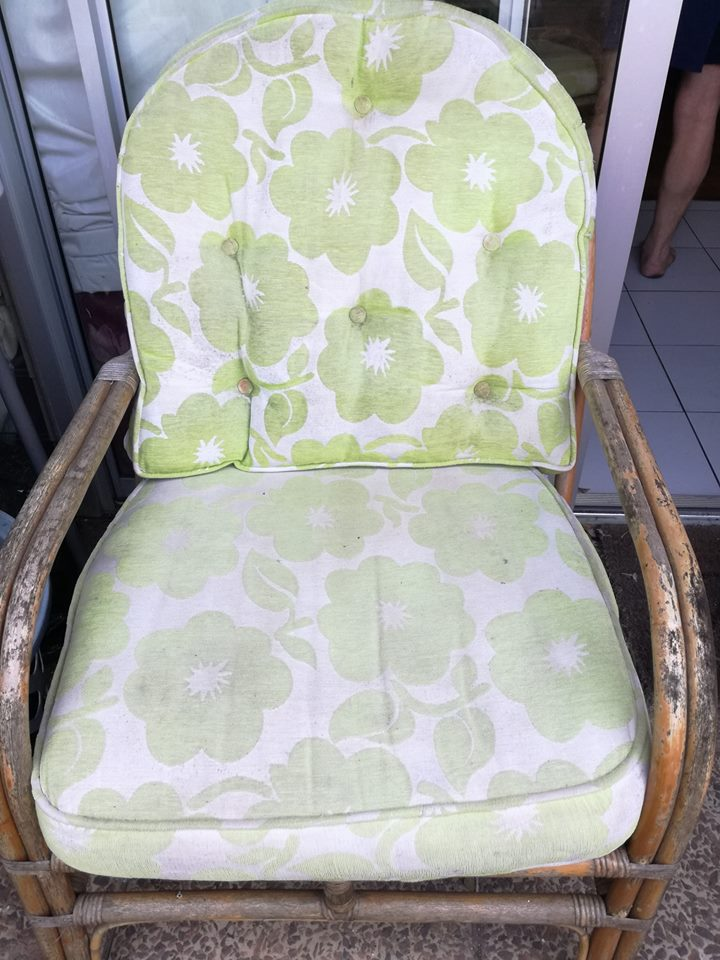 Cane chair with green pillows for sale