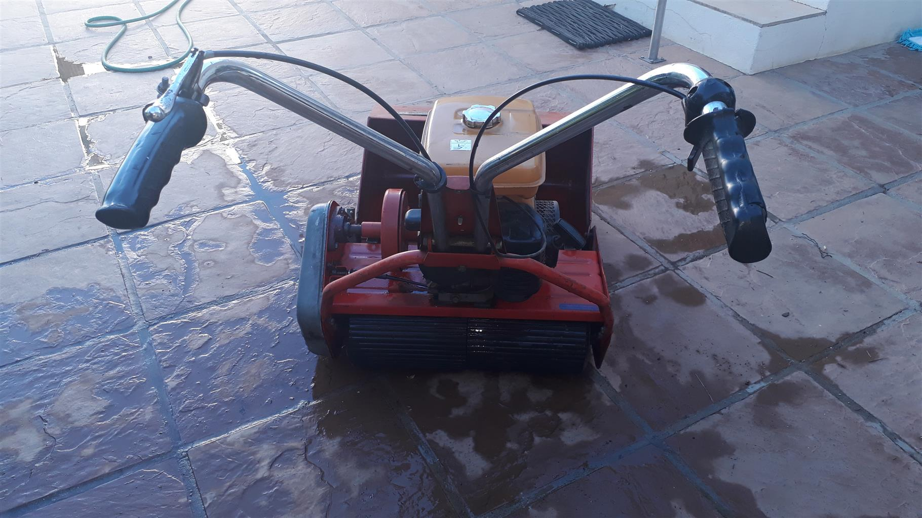 Self-propelled roller petrol lawnmower
