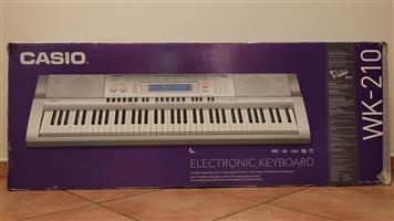 Casio WK210 76-Key Digital Keyboard with dynamic touch keys and stand.