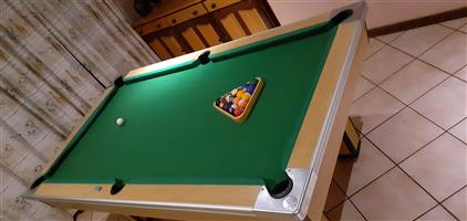 Pool table complete with balls and cue sticks.