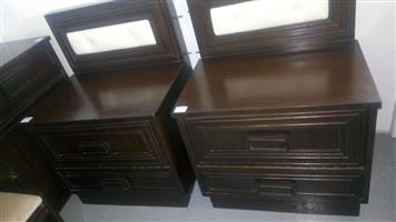 Dark wooden bedside drawers with white material