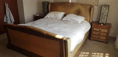 Double bed with wooden base frame and side cabinets