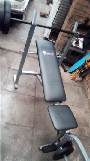 Gym training bench with two sets of free weight set's for sale.