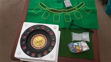 Roulette wheel and chips and glasses and playing mat