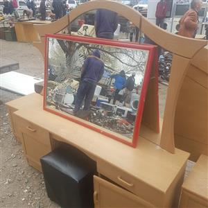 Light wooden dresser and red framed mirror
