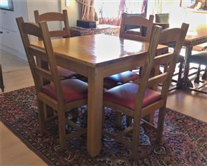 Solid 4 seater oak dining room suite with 4 matching chairs. Chairs have drop in seats and are high backed.Recently reupholstered. Excellent condition.