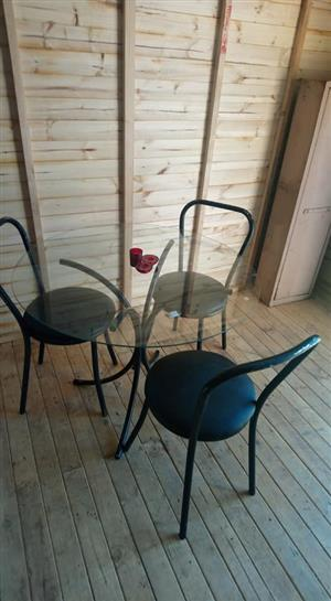 Glass top round table with 3 black chairs