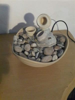 Small water feature bubbling over small pebbles Desktop