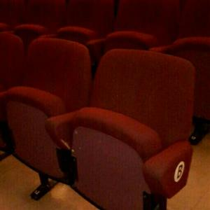 500 Used civic tip up chairs upholstered in burgundy fabric.The chairs are still in good condition.