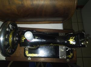 Selling a old anitique singer sewing machine R1000 hand operated priced to go with the box.A 1912 Singer sewing machine for sale in working condition. In box with cover. Transverse shuttle type. With original key for cover. Includes a few attachments.