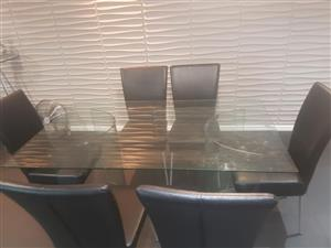 Glass Dining table with 6 chairs for sale.
