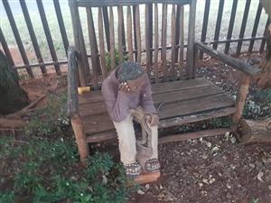 Wooden garden bench with african man