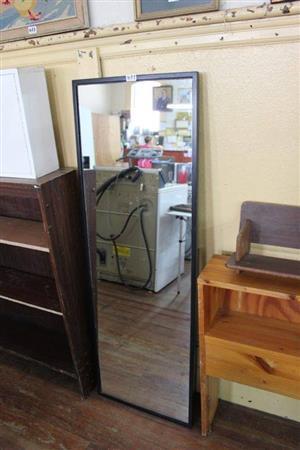 Tall dark wooden framed mirror