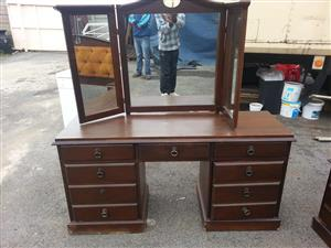 Dark wooden dresser with drawers and folding mirrors