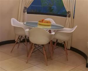 Round glass top table with 4 white chairs