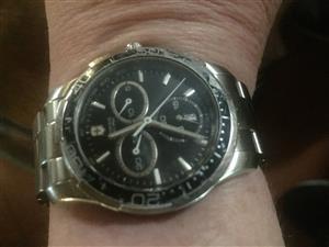 an original victorinox chrome watch with a black face